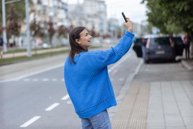 Uma jovem faz uma selfie para a câmera do telefone na rua.