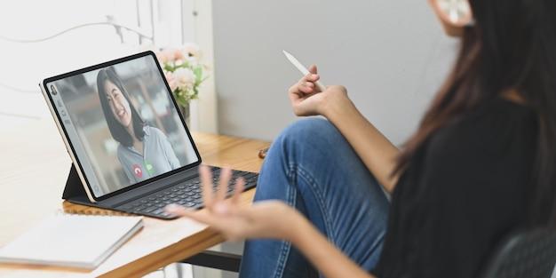 Uma jovem fazendo videoconferência com colegas na mesa de trabalho de madeira