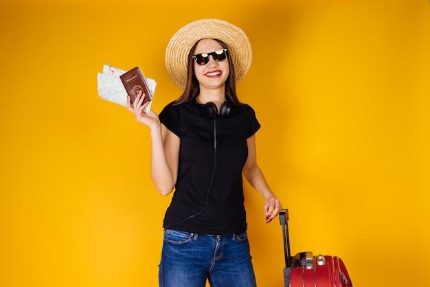 Uma jovem feliz com um chapéu e óculos escuros sai de férias, viaja, tem passagens aéreas e um passaporte