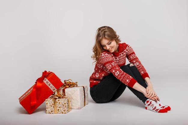 Uma jovem feliz com um suéter vintage sentado perto dos presentes