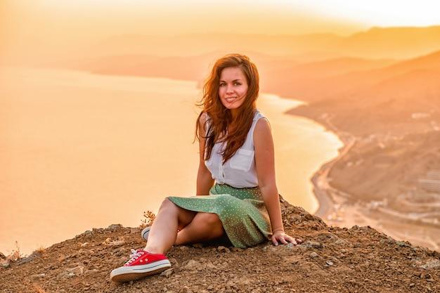 Uma jovem feliz de saia está sentada no topo de um penhasco sob o céu do pôr do sol