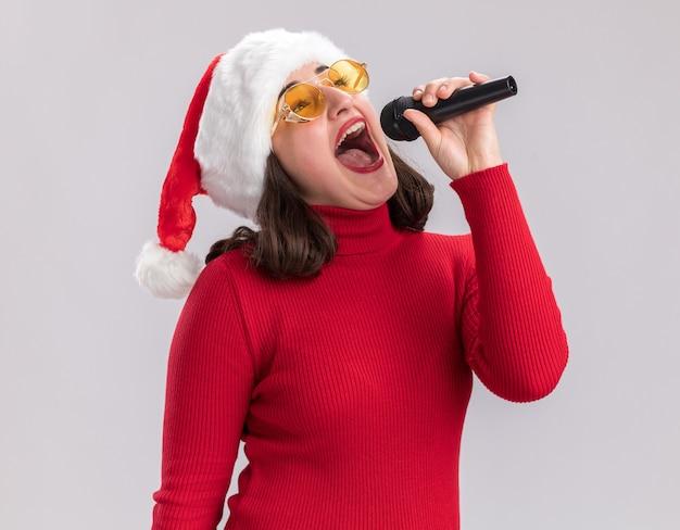 Uma jovem feliz e alegre com um suéter vermelho e um chapéu de papai noel usando óculos, segurando o microfone, cantando uma música em pé sobre uma parede branca
