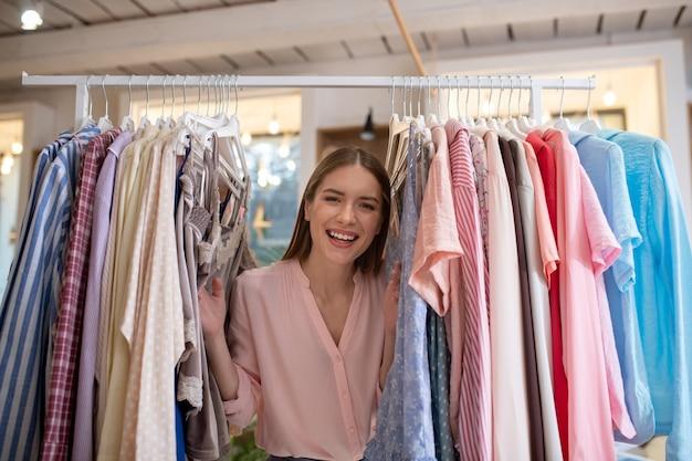 Uma jovem feliz e sorridente em pé entre roupas no ateliê