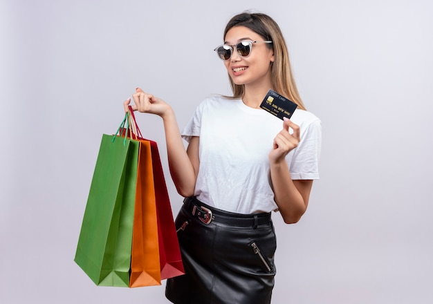 Uma jovem feliz em uma camiseta branca usando óculos escuros e mostrando o cartão de crédito enquanto segura sacolas de compras em uma parede branca