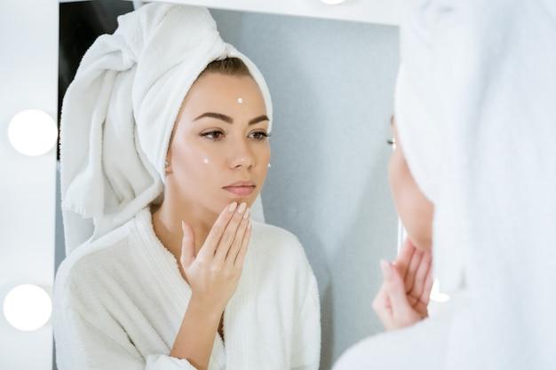 Uma jovem feliz em uma toalha em frente a um espelho passa creme no rosto, um conceito de cuidados com a pele em casa