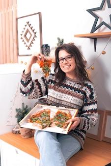 Uma jovem feliz está animada com a pizza encomendada.