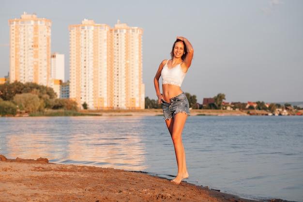 Uma jovem feliz está de pé na areia uma bela loira sorridente em um top curto e desabotoado ...