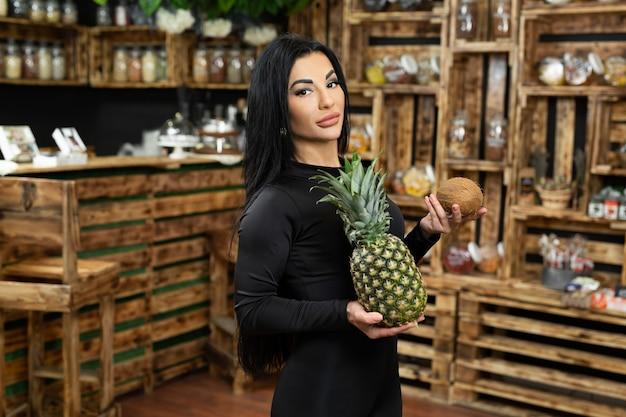 Uma jovem feliz está segurando e vendendo frutas frescas em uma loja de produtos naturais.