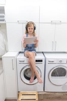 Uma jovem feliz ouve música em fones de ouvido segurando o tablet na lavanderia com máquina de lavar