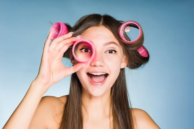 Uma jovem feliz quer ser bonita, na cabeça e nas mãos grandes rolos cor-de-rosa