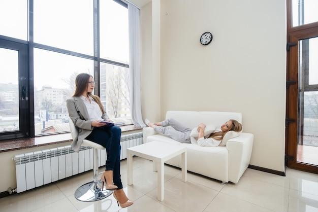 Uma jovem feliz se comunica com um psicólogo em um escritório moderno