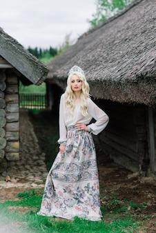 Uma jovem fêmea de aparência eslava com coroa, kokoshnik no meio do verão, vila, herdade