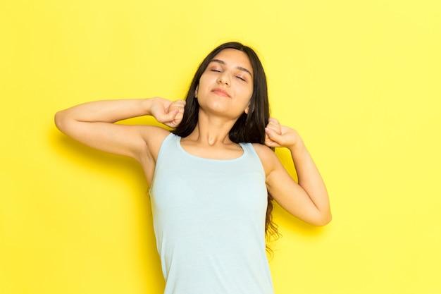 Uma jovem fêmea de camisa azul posando e espirrando no fundo amarelo.