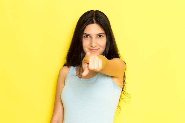 Uma jovem fêmea de camisa azul posando e sorrindo com o dedo apontado para o fundo amarelo.