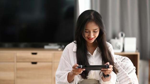 Uma jovem fêmea de pijama, jogando videogame e sentada no sofá em casa.