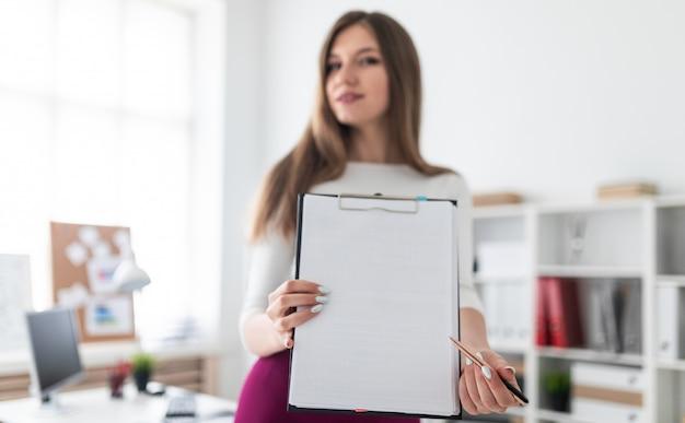 Uma jovem fica perto da mesa do computador e detém um tablet com uma folha branca.