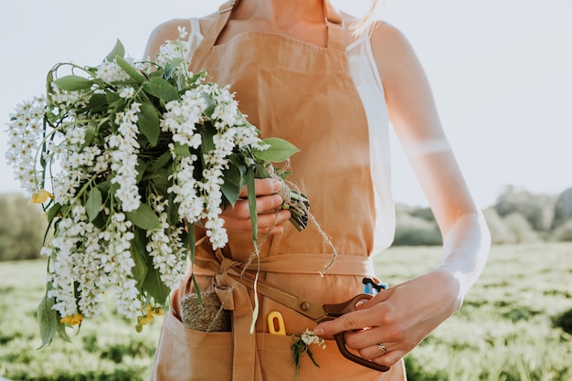 Uma jovem florista de avental está criando um buquê floral como um presente da florista de flores silvestres no trabalho pequena empresa florista mulher segurando um elegante buquê de flores