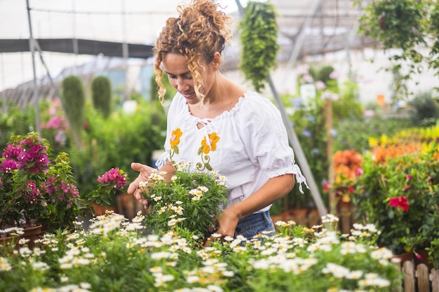 Uma jovem florista que trabalha em uma estufa com muitas mudas admira o crescimento de flores brancas como as margaridas. conceito de cuidado e paixão pela natureza