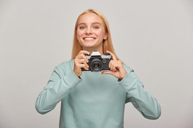 Uma jovem fotógrafa parece feliz sorrindo, segurando uma câmera fotográfica retro vintage nas mãos