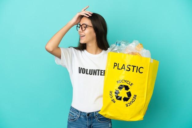 Uma jovem francesa segurando um saco cheio de garrafas de plástico para reciclar percebeu algo e pretendia encontrar a solução