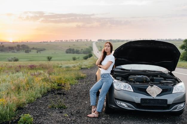Uma jovem frustrada fica perto de um carro quebrado no meio da rodovia durante o pôr do sol. avaria e reparação do carro. esperando por ajuda.