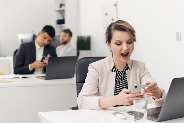 Uma jovem funcionária de um banco ou seguradora está entediada e boceja no local de trabalho. rotina do escritório.