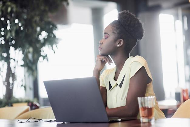 Uma jovem garota afro-americana com cabelos cacheados escuros, ponderando sobre um laptop em um café