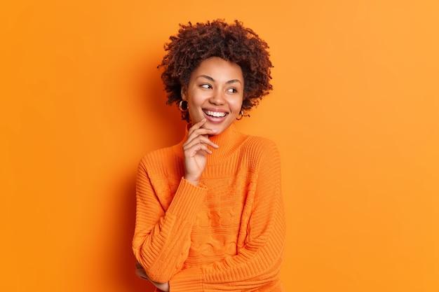 Uma jovem garota afro-americana olha de lado com um sorriso cheio de dentes e percebe que algo agradável tem uma expressão despreocupada vestida em poses casuais de macacão contra uma parede laranja vívida