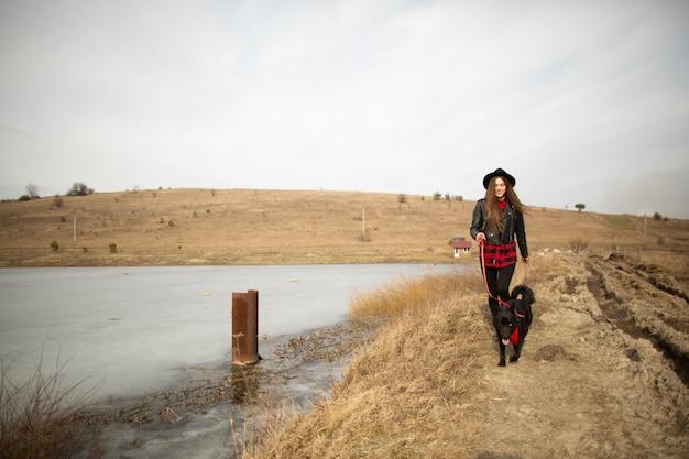 Uma jovem garota anda com um cachorro na margem de um lago
