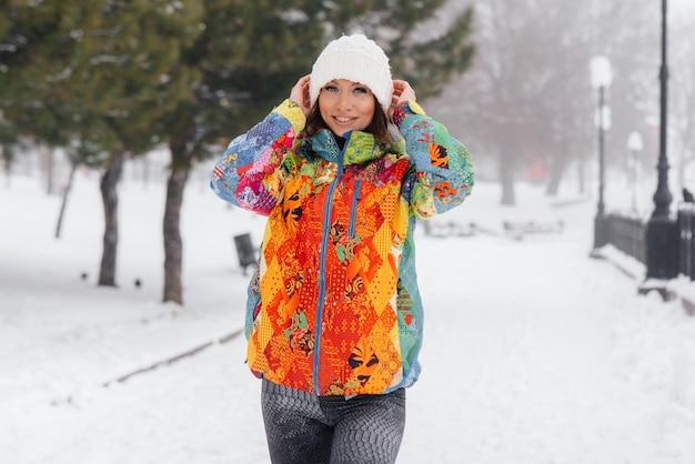 Uma jovem garota atlética posa em um dia gelado e com neve. fitness, corrida.
