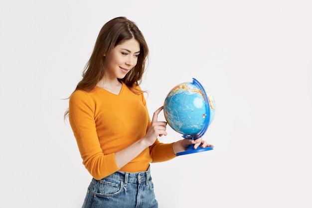 Uma jovem garota atraente escolhe um lugar para descansar em um grande globo. férias, viagens
