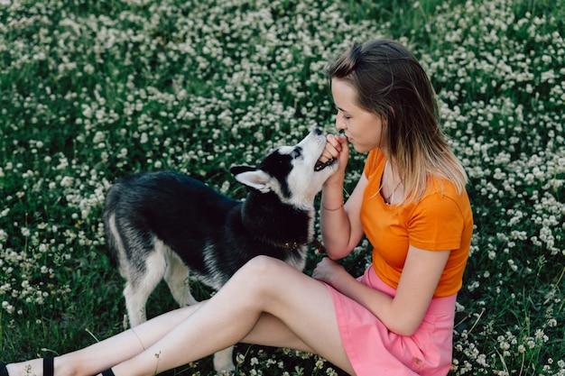 Uma jovem garota bonita com cabelo loiro está sentado no pasto com seu filhote de cachorro husky e brincando.