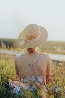 Uma jovem garota bonita com um chapéu de palha sentado para a câmera no campo