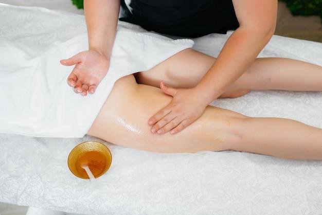 Uma jovem garota bonita está desfrutando de uma massagem profissional usando mel no spa. cuidados com o corpo. salão de beleza.