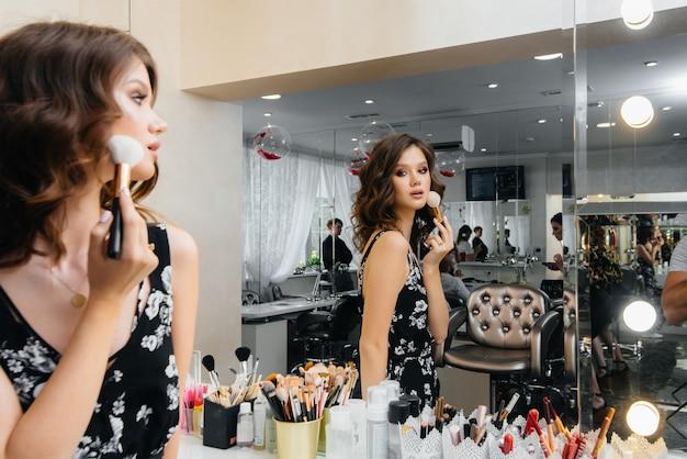 Uma jovem garota bonita faz uma maquiagem linda noite em frente ao espelho. moda e beleza.