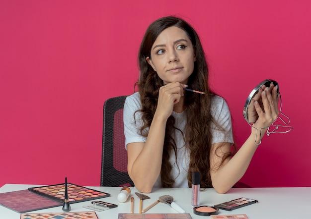 Uma jovem garota bonita sentada à mesa de maquiagem com ferramentas de maquiagem segurando um espelho e uma escova de sombra, olhando para o lado e tocando o queixo isolado no fundo carmesim