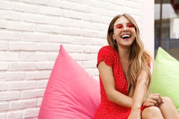 Uma jovem garota bonita sentada em um café ao ar livre em um pufe rosa e rindo