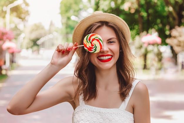 Uma jovem garota caminha no parque e tem nas mãos um pirulito multicolorido de forma redonda. a garota em um chapéu de palha, sorrindo no parque e cobre um olho com doces
