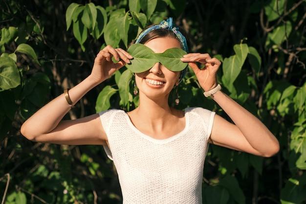 Uma jovem garota com aparelho sorri brilhantemente num dia ensolarado de verão, fecha os olhos com folhas verdes.