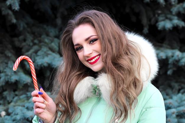 Uma jovem garota com cabelo loiro encaracolado com maquiagem brilhante e lábios vermelhos com um sorriso segura um doce de natal.