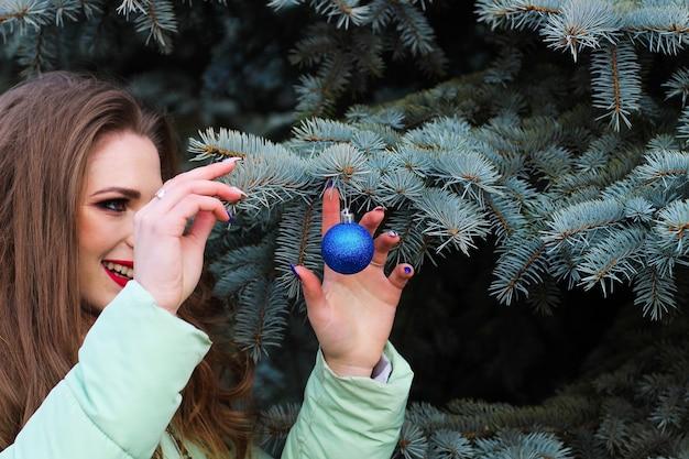 Uma jovem garota com cabelo loiro encaracolado com maquiagem brilhante segurando um brinquedo de natal.