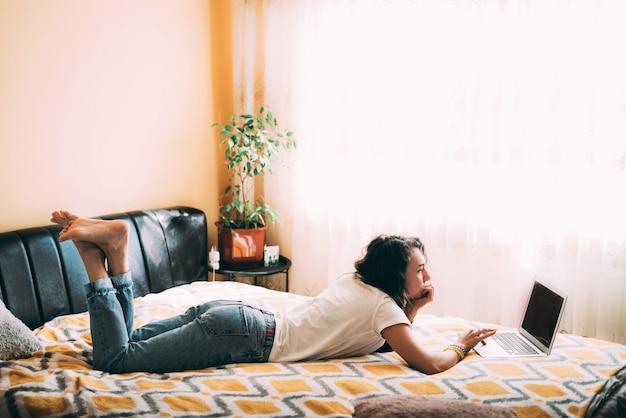 Uma jovem garota com cabelos cacheados em uma camiseta branca e calça jeans deitada na cama e olha para o laptop.
