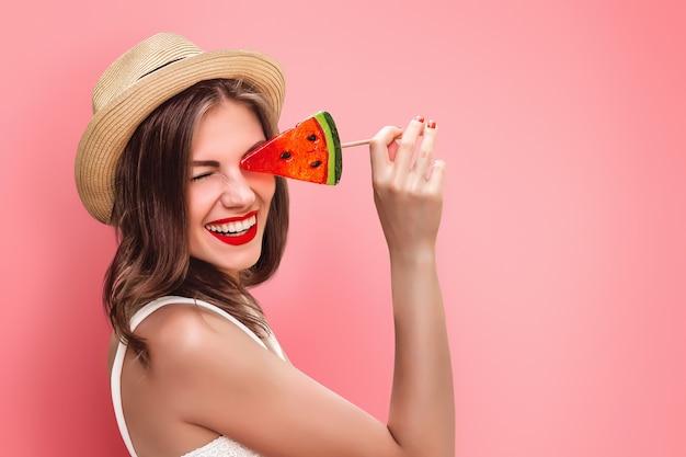 Uma jovem garota com chapéu de palha com um pirulito e batom vermelho, sorrindo em uma parede rosa. garota feliz cobre os olhos com doces tolos e ri. garota turista se divertindo