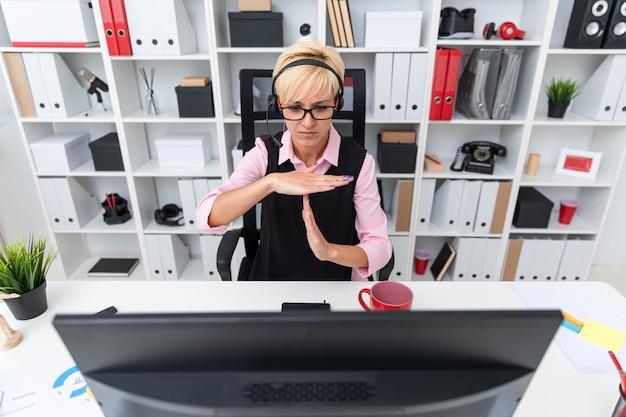Uma jovem garota com fones de ouvido, sentado à mesa do computador e mostra as palmas das mãos do sinal.