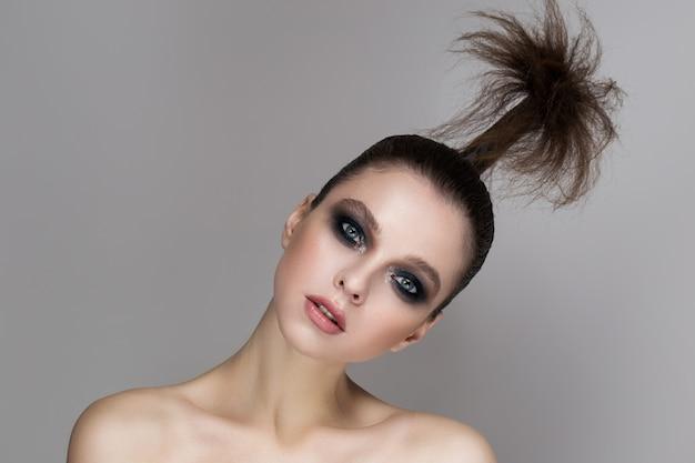 Uma jovem garota com maquiagem brilhante e pele radiante.