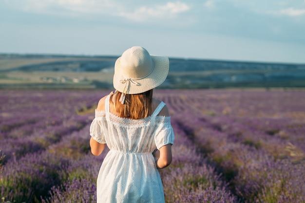 Uma jovem garota com um chapéu e um vestido branco fica de costas em um campo de lavanda
