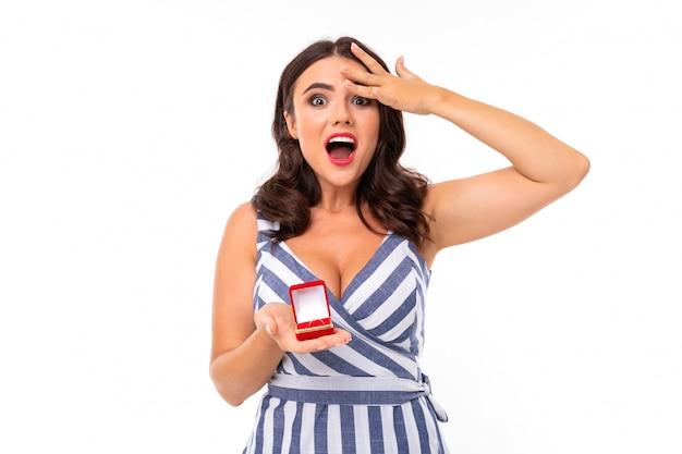 Uma jovem garota com um sorriso encantador, dentes lisos, batom vermelho, cabelos castanhos compridos e ondulados, maquiagem linda, em um vestido branco e azul em uma faixa com um decote, segura uma caixa de anel vermelha nas mãos