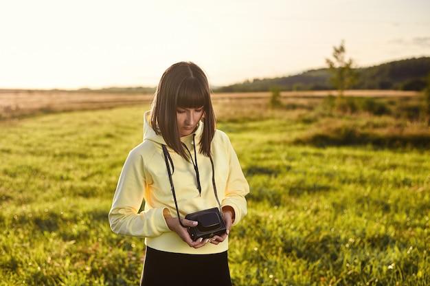 Uma jovem garota com uma câmera nas mãos encontra o amanhecer no campo.
