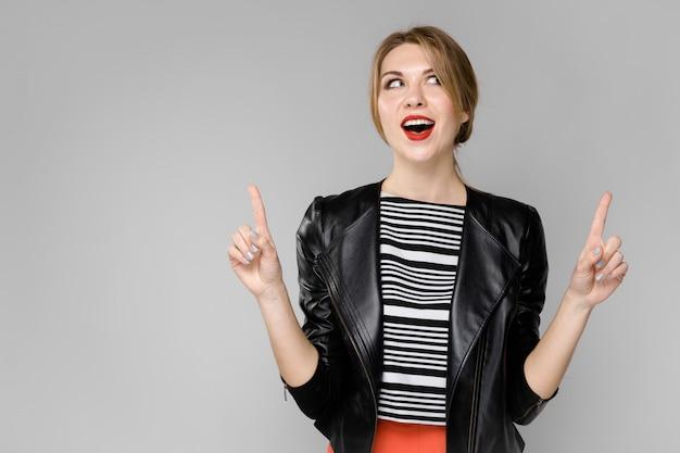 Uma jovem garota com uma jaqueta de couro mostra nas mãos o indicador. retrato de uma menina com cabelos loiros em uma jaqueta de couro