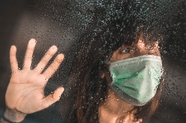 Uma jovem garota com uma máscara na pandemia de covid-19, olhando pela janela